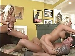 Two tanned busty blondes share one stiff cock on the floor