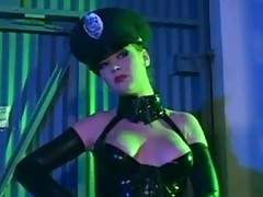 Audrey Hollander in a cop uniform and latex molesting a guy